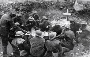 Soldiers on the Western Front in a happy mood as they eat a meal to celebrate Christmas Day in a shell hole partly occupied by the grave of a comrade.